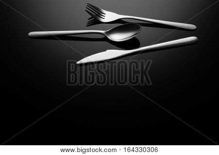 Black food background. Stainless steel, modern silverware on black background with reflection. Image with copy space. Symbol or concept for diners, cafes and good food competitions and festivals