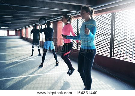 Side view of athletic people playing ball and doing cardio exercise in parking. Copyspace