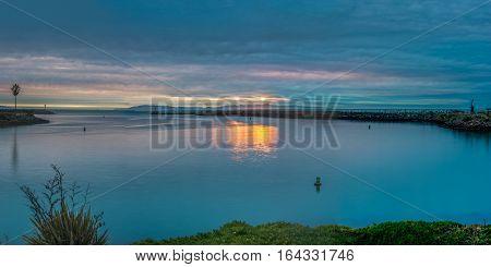 Panoramic sun sets behind Santa Cruz Island as boats return from open water into Ventura Harbor.