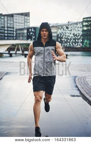 Sportive And Healthy Male Running Down Street