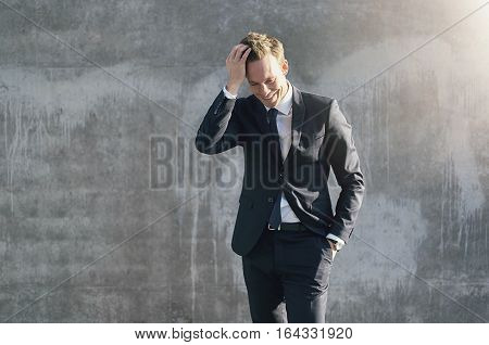 Smiling Businessman Posing On Grey Wall