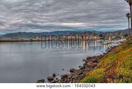Panoramic of overcast sky reflected in Ventura Marina water at dusk.