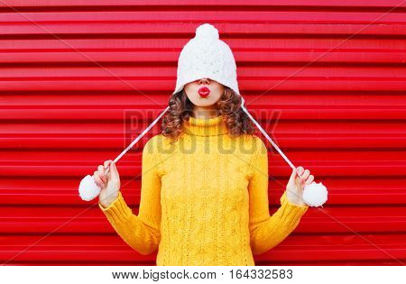 Fashion Happy Woman Blowing Red Lips Makes Air Kiss Wearing Colorful Knitted Hat, Yellow Sweater Ove