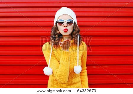 Fashion Woman Blowing Red Lips Makes Sends Air Kiss Wearing Colorful Knitted Sweater Over Red Backgr