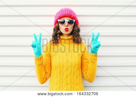 Fashion Woman Blowing Red Lips Wearing Colorful Pink Hat Knitted Yellow Sweater In Gloves Over White