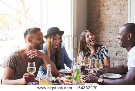 Young Friends Having Dinner And Laughing Together