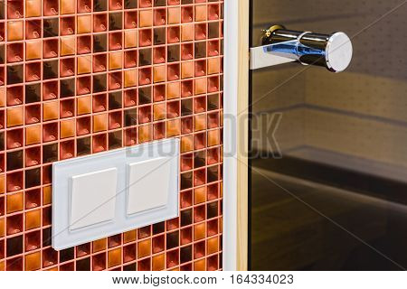 Fragment of the interior bathroom with a  light switches and a door handle in a sauna