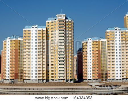 New district with constructed buildings near river over clear cloudless blue sky closeup