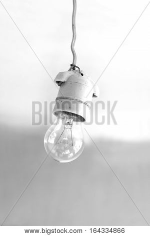 Turning off an electric light bulb in ceramic holder hanging on wire close-up. Black and white photography