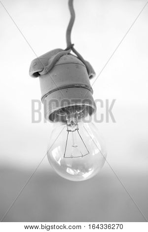 Turning off electric light bulb in ceramic holder hanging on wire close-up. Black and white photography
