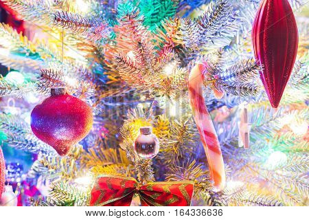Christmas tree decorations.  Dazzling bright white and glowing red christmas holiday tree ornaments and candy cane hanging from branches on a small faux indoor tree, decorated with a bowtie.
