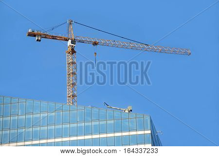Yellow hoisting tower crane on top of construction skyscraper building over cloudless blue sky