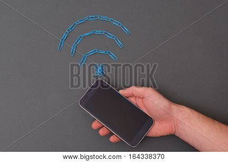 Wireless Signal Symbol Made Of Paperclips And Mobile Phone