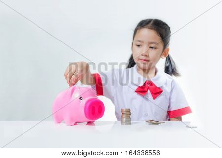 Asian little girl in Thai student uniform putting coins to piggy bank selective focus on pig shallow depth of field