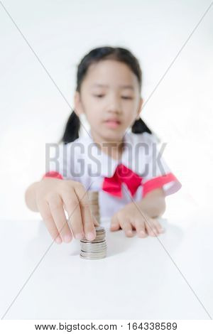 Asian little girl in Thai student uniform stacking coins Select focus on hand shallow depth of field