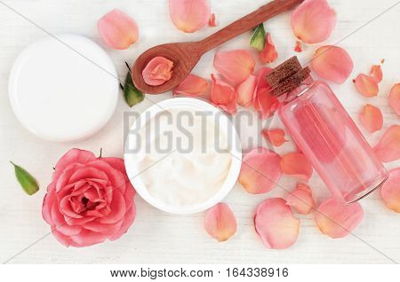 Skincare beauty treatment plant-based products with wink rose petals. Jar of body moisturizer, attar bottle toning lotion, top view homemade cosmetic ingredients.