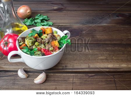 beef meat stewed with potatoes, carrots and spices in ceramic pot with ingredients on wooden background