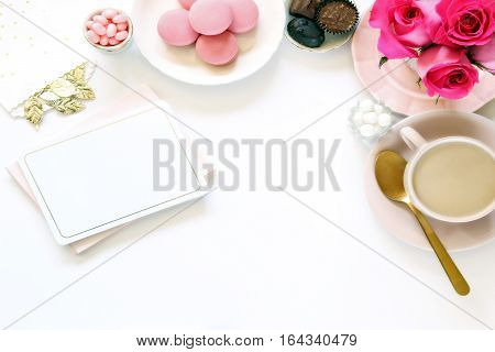 Romantic desktop with pink colors, coffee, sweets and stationary. Open space for copy.