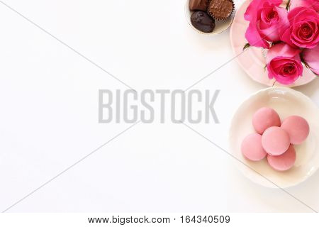 Romantic desktop with chocolates, hot pink roses, and pink macaroons.