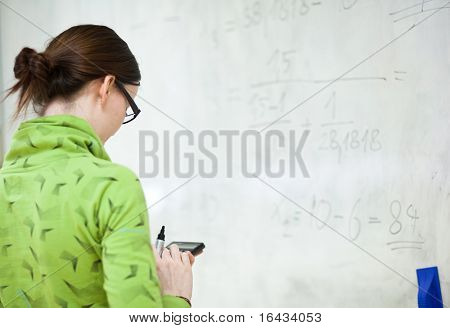 young female college student in front of a whiteboard using a calculator during math class
