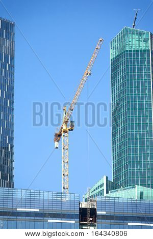 Yellow hoisting tower crane on top of office construction office buildings over blue sky