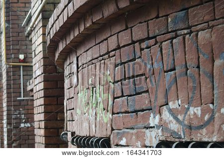 a semi-circular wall of red bricks with painted