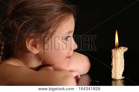 Portrait of a Girl 4-5-6 years, looking at burning candle isolated on black background.