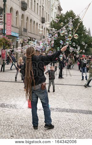PRAGUE, CZECH REPUBLIK - OCTOBER 18, 2016: A street artist in the Old Town of Prague, makes soap bubbles and entertain tourists from all over the world