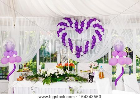 beautiful wedding decorations. Heart of white and purple balloons on a celebratory table