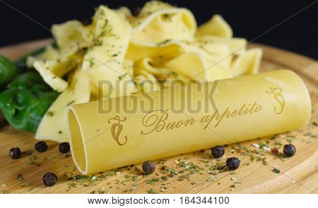 On a wooden board is in the foreground a cannelloni with the lettering - bon appetite - in italian words. In the background are further noodles garnished with leaf spinach and pepper grains