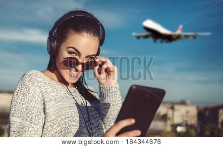 Young woman ordering air ticket by tablet outdoor online shopping wireless technology