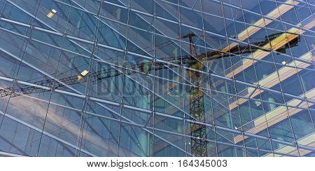 Visual illusion of constitution crane trapped inside the glass building. Reflection of construction crane in a modern glass building.