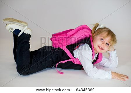 Portrait Of Young Lying Schoolgirl With Schoolbag