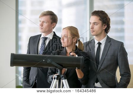Group of business people standing near the window with optic telescope, analyzing market to build successful business plan, spying for rivals, new business horizon, targeting. Business vision concept