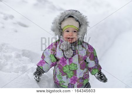 Happy little boy is playing with snow on winer background.
