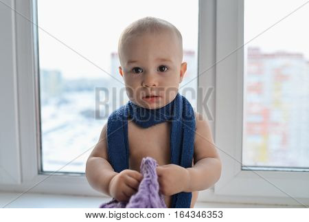 Happy little baby boy standing near the window weared in winter hat and scarf, city at background.