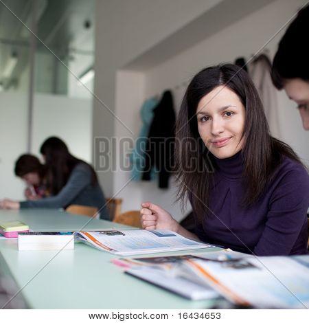 junge hübsche weibliche College-Studentin, die sitzen in einem Klassenzimmer voller Studenten während des Unterrichts