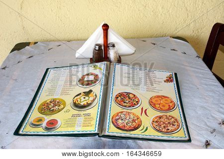 BALI, CRETE - SEPTEMBER 16, 2016 - Pizza and salad menu displayed on a dining table at the Greek Taverna Valentino edge of the beach Bali Crete Greece Europe, September 16, 2016.