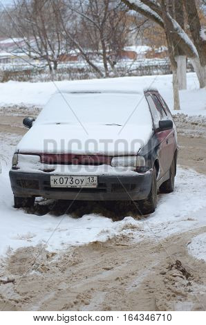 SARANSK, RUSSIA - JANUARY 1, 2017: Old forsaken car cowered by snow.