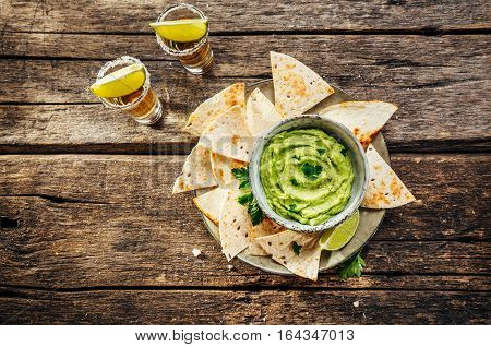 Nachos on plate and avocado sauce and tequila shots with lime for drinking. Rustic style, top view