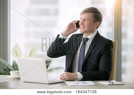 Young smiling handsome businessman working with laptop at the desk in modern office, talking on phone, planning future meetings, developing business goals, making call on smartphone. Business concept