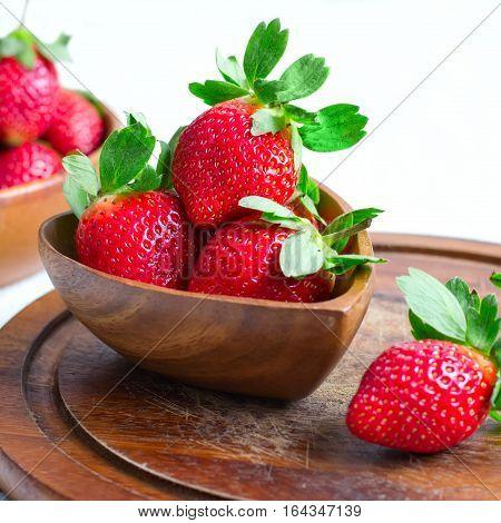 Wooden bowl with a luscious garden strawberries closeup, selective focus