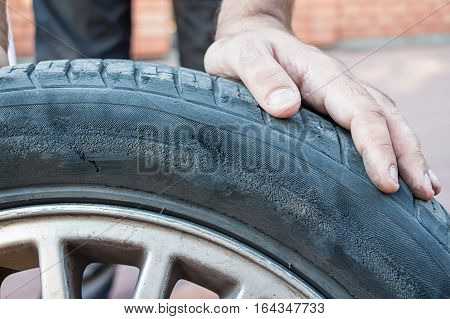 Mechanician changing unserviceable car wheel in auto repair shop