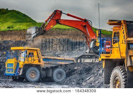 NOVOKUZNETSK, RUSSIA - JULY 26, 2016: Big yellow mining trucks and excavators at worksite