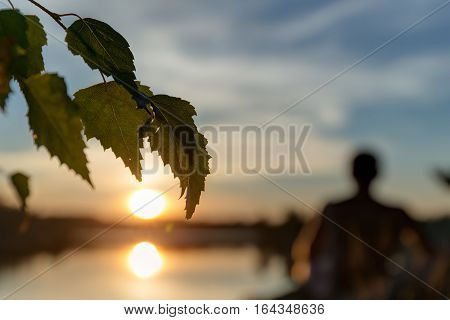 silhouette of man admiring the sun at sunset