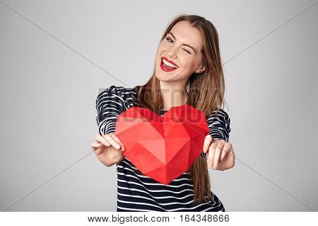 Playful emotional woman with red lips showing red polygonal paper heart shape winking at camera