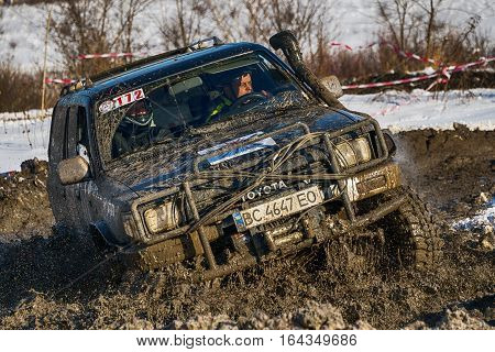 Lviv Ukraine - December 04 2016: Unknown racers on off-road vehicle Nissan overcomes the track at amateur competitions among off-road vehicles near ringroad of the city Lviv Ukraine
