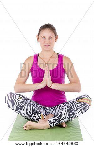 Sporty beautiful young woman practicing yoga, sitting in Padmasana, Lotus posture, asana for meditation, pranayama working out wearing black sportswear, studio, full length