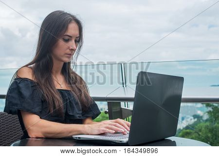 Young female freelancer dressed in black working on a project on laptop computer while sitting at rooftop cafe terrace.