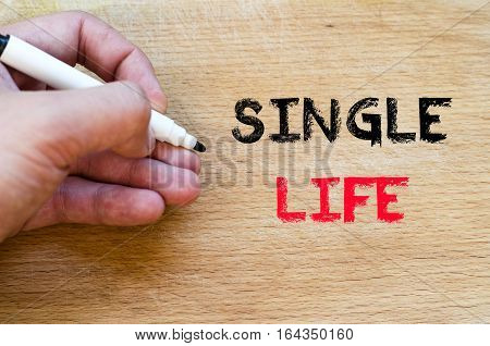 Human hand over wooden background and single life text concept